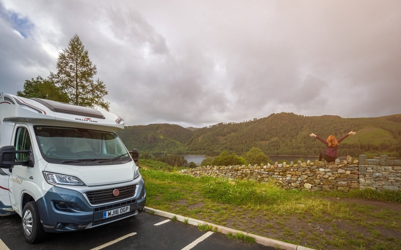 Luxury motorhome parked by the side of a lake, with girl sat on a wall admiring the view in the lake district.