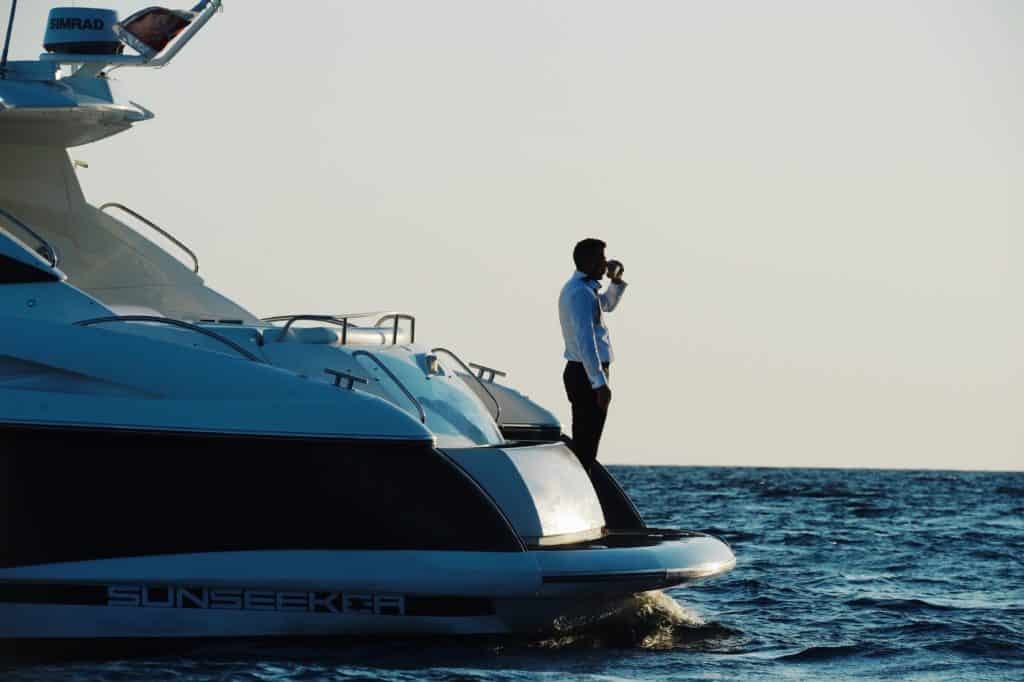 Man-Standing-on-Yacht-at-sunset
