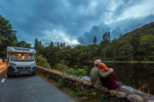 Couple say on a wall in front of a lake beside their motorhome.